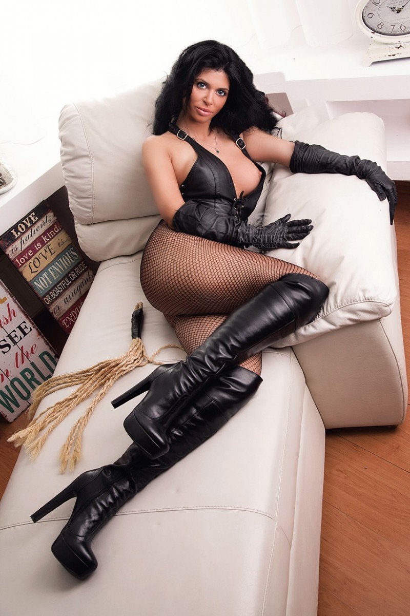 Mistress Antonella in leather suit on a couch waiting to be worshiped by slaves