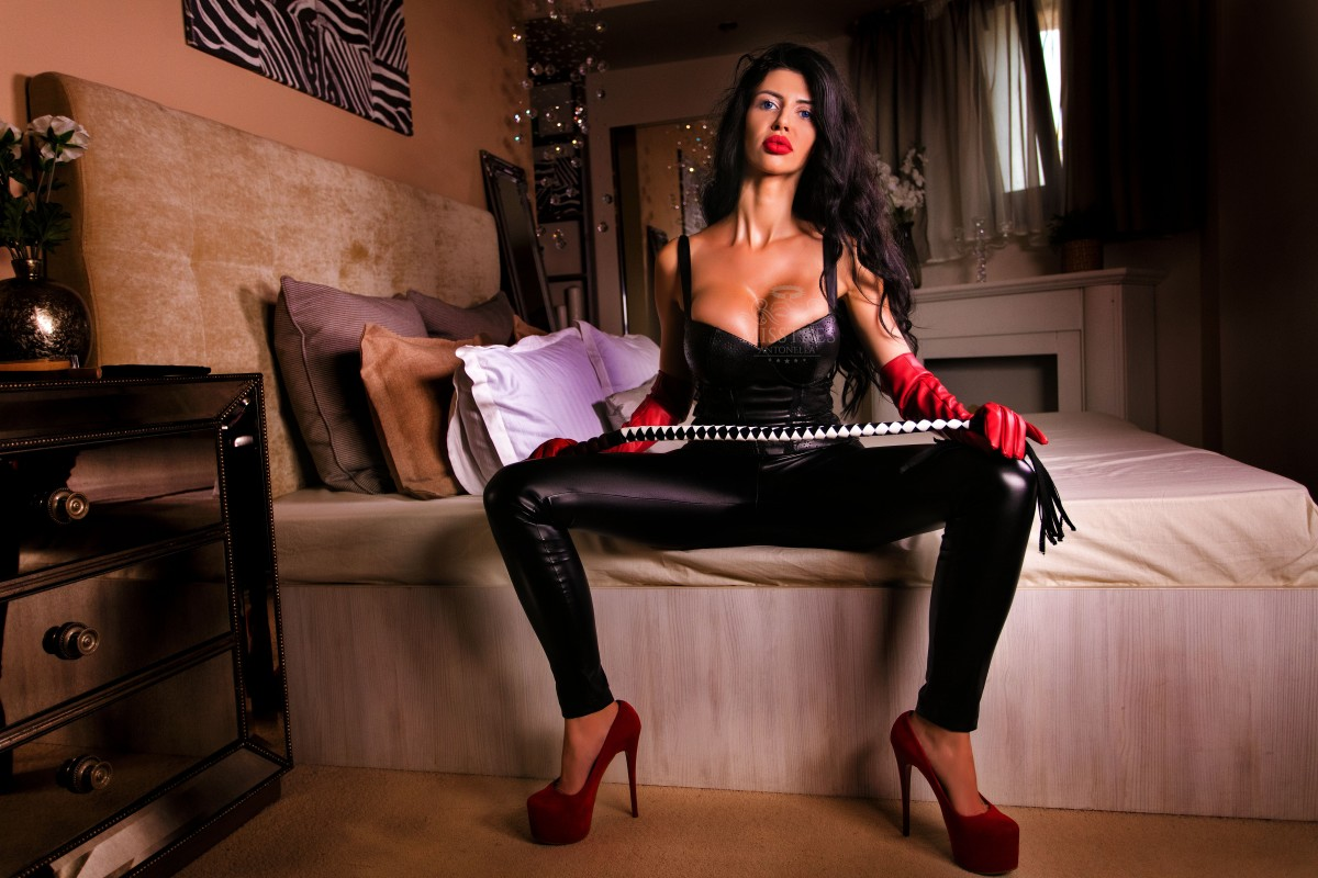 mistress antonella on the bed ready to whip a sissy slave