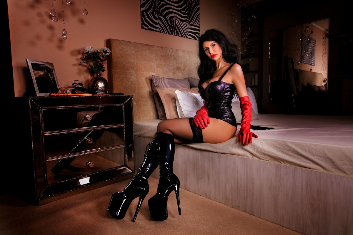 mistress antonella sexy in black boots and stockings with red latex gloves