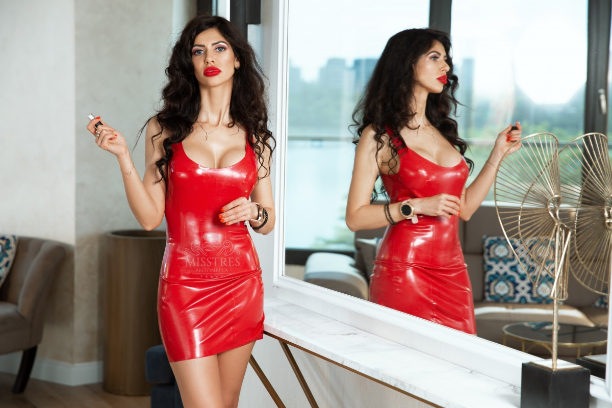 mistress antonella puts some red lipstick to match the red latex dress