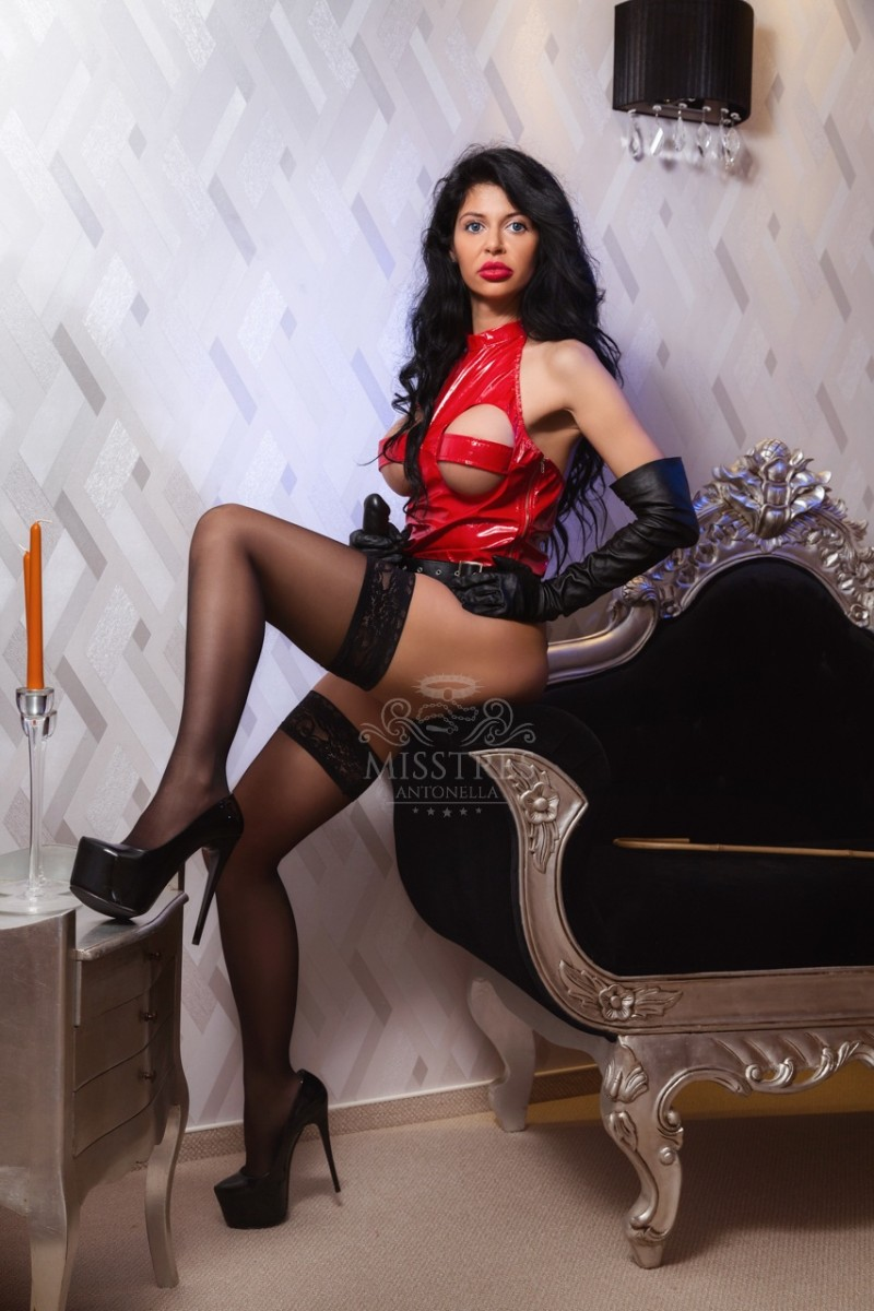 Mistress Antonella in red latex suit and black stockings