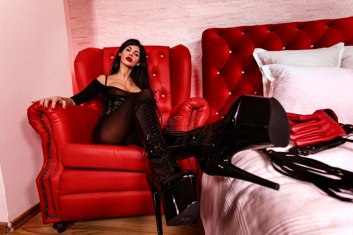mistress antonella high heels boots on the red leather chair